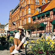 Eine Frau sitzt auf einer Bank in Ystad.