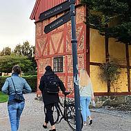 Drei Personen spazieren vor einem Fachwerkhaus in Ystad