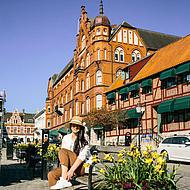 Frau mit Hut auf Bank in Ystad.