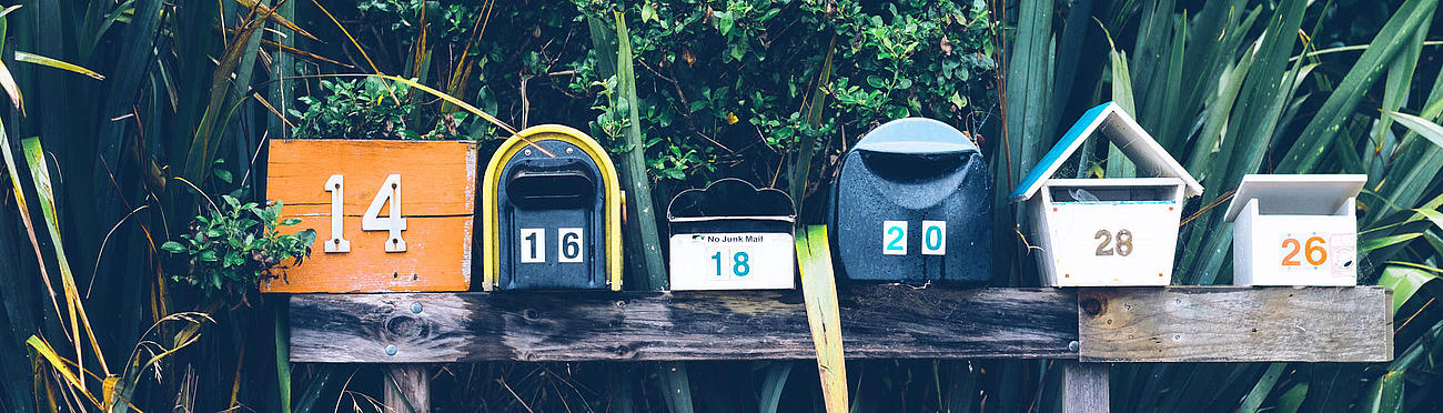 Colourful mailboxes on a bench.