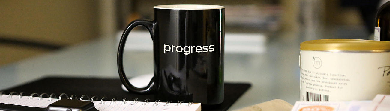 "Cup with imprint ""progress"" on a desk."