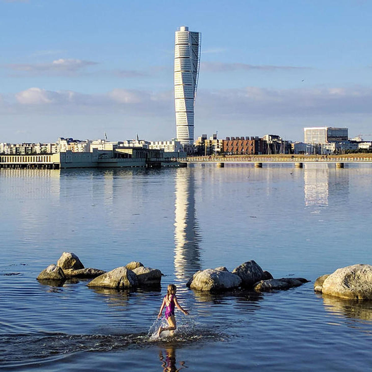 The Turning Torso Malmö is reflected in the water.