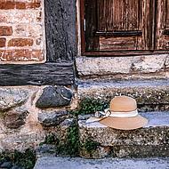 Ein Strohhut liegt auf einem Treppenabsatz.