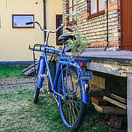Blaues Fahrrad vor einem Haus.